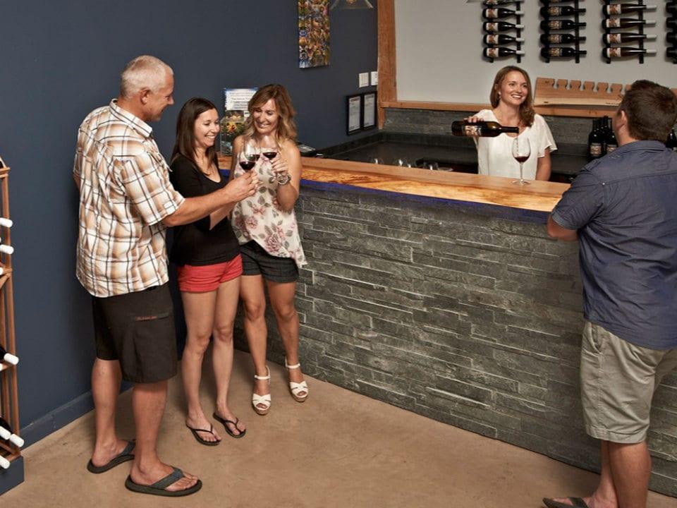 vignoble salle de dégustation avec employée au bar et clients en train de goûter aux vins nighthawk vineyards okanagan falls colombie britannique canada ulocal produits locaux achat local produits du terroir locavore touriste