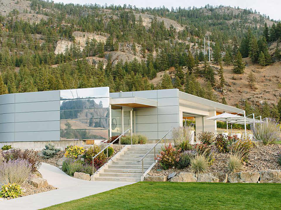 vineyard white modern building with steps rising to the terrace with greenery and mountain in the back painted rock estate winery penticton british colombia canada ulocal local products local purchase local produce locavore tourist