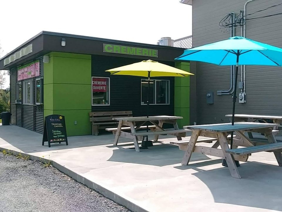 pastry shops green and dark brown building pastry and dairy with terrace picnic tables and parasol pâtisserie la vitrine sherbrooke quebec canada ulocal local products local purchase local produce locavore tourist