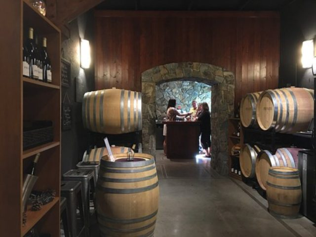 vineyard wine cellar with cedar barrels and tasting room at the bottom with customers privato vineyard and winery kamloops british colombia canada ulocal local products local purchase local produce locavore tourist