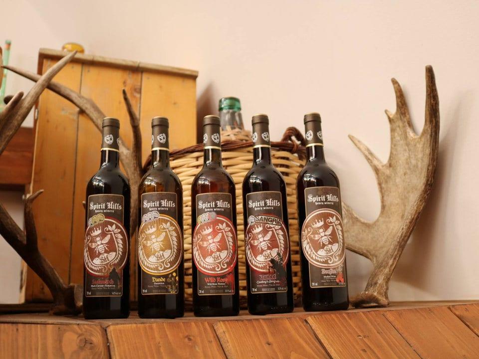 vignoble 5 bouteilles de différents vins sur une tablette de bois avec les bois d'un orignal spirit hills honey winery millarville alberta canada ulocal produits locaux achat local produits du terroir locavore touriste