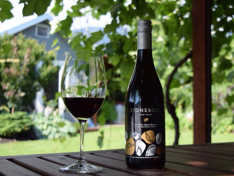 vignoble verre et bouteille de vin rouge sur une table avec vignoble en arrière-plan stoneboat vineyards oliver colombie britannique canada ulocal produits locaux achat local produits du terroir locavore touriste