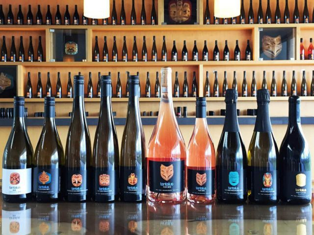 vignoble plusieurs variétés de vin de la maison sur le bar avec un mur décoré de bouteilles de vins tantalus vineyards kelowna colombie britannique canada ulocal produits locaux achat local produits du terroir locavore touriste