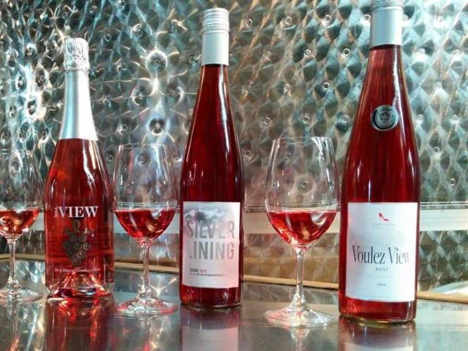 vignoble 3 bouteilles de différents rosés avec leur verre sur une table en stainless et mur the view winery kelowna colombie britannique canada ulocal produits locaux achat local produits du terroir locavore touriste