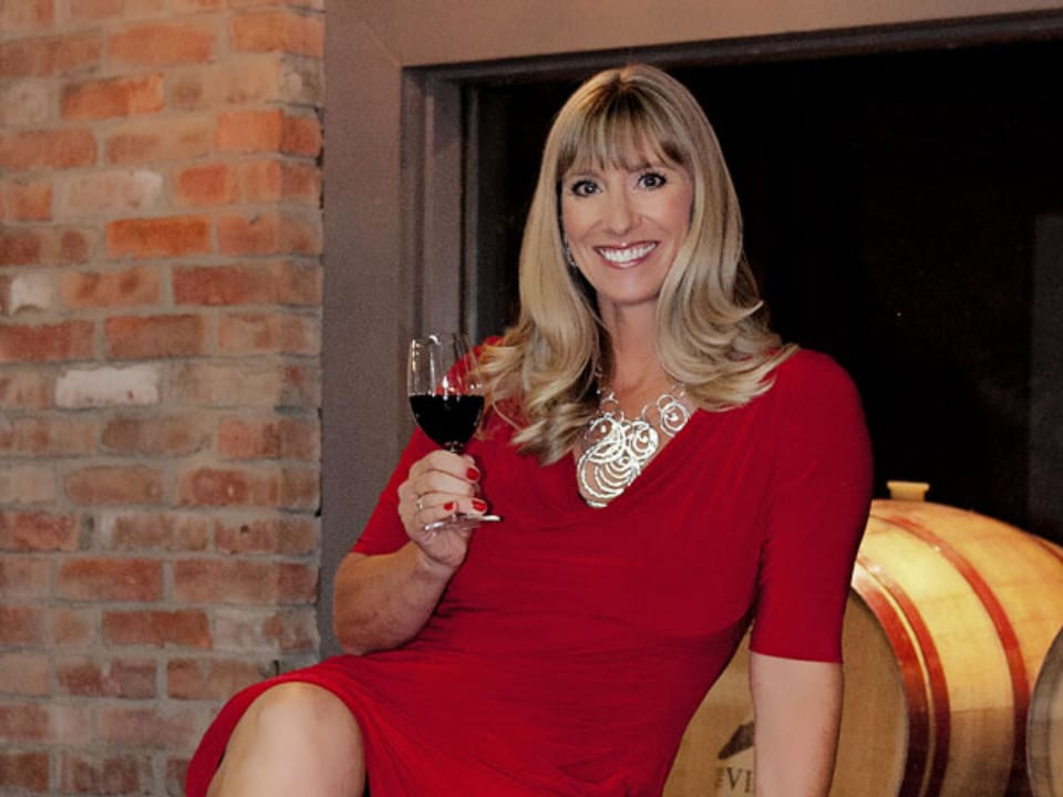 vignoble jennifer molgat présidente assise devant un tonneau de bois avec un verre de vin à la main the view winery kelowna colombie britannique canada ulocal produits locaux achat local produits du terroir locavore touriste