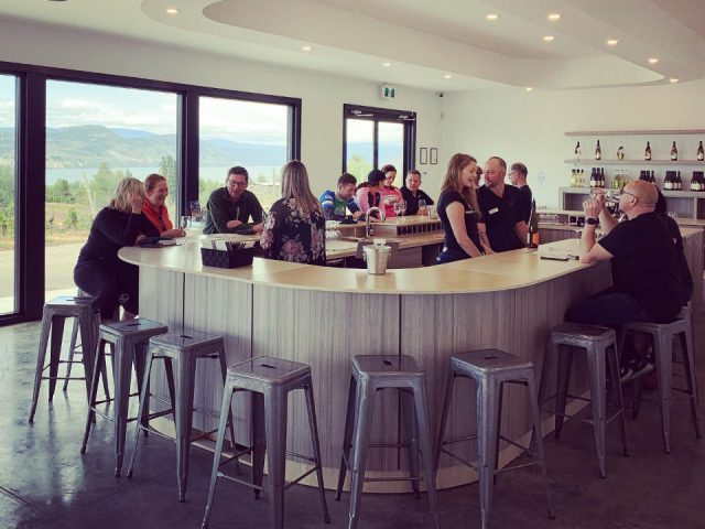 vignoble clients en train de goûter aux vins dans la salle de dégustation autour du bar avec grande fenêtre sur le vignoble therapy vineyards and inn naramata colombie britannique canada ulocal produits locaux achat local produits du terroir locavore touriste