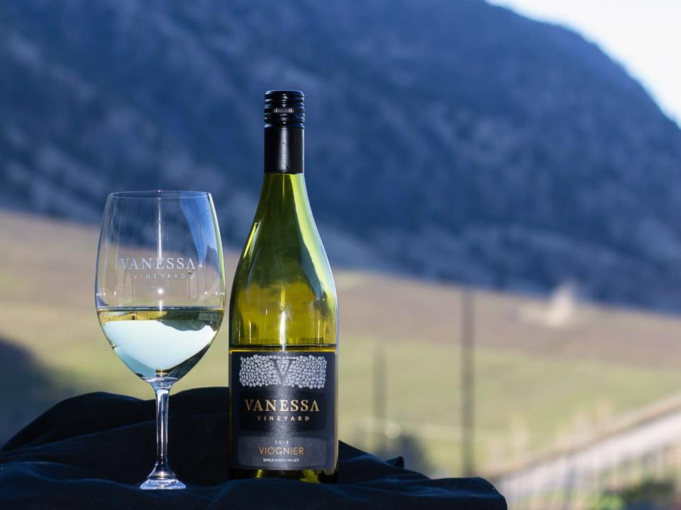 vineyard glass of white wine and bottle beside with vineyard in the backgroundvanessa vineyard cawston british colombia canada ulocal local products local purchase local produce locavore tourist