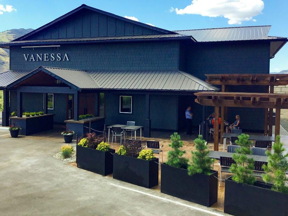 vignoble bâtisse extérieure bleu avec terrasse sur le côté avec clients vanessa vineyard cawston colombie britannique canada ulocal produits locaux achat local produits du terroir locavore touriste