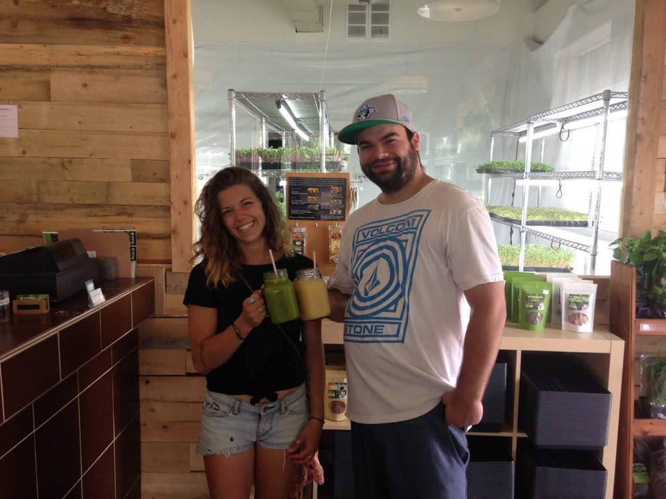 produce markets 2 satisfied customers and energized by their green sprout juice in the shop vertige ferme urbaine sherbrooke quebec canada ulocal local products local purchase local produce locavore tourist