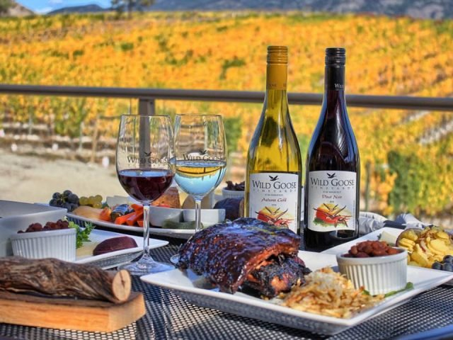 vineyard on the patio of winemaker's bbq plate accompanied by 2 bottles of wine and 2 glasses with views of the vineyard wild goose winery okanagan falls british colombia canada ulocal local products local purchase local produce locavore tourist