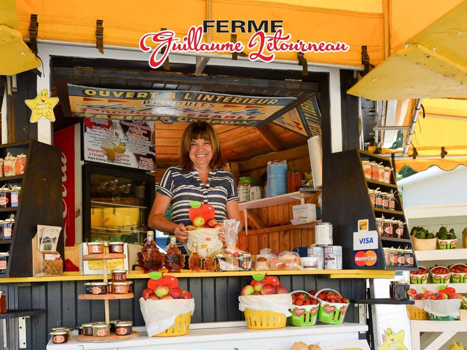 produce picking kiosk of fruits and vegetables at the entrance with employee who welcomes you ferme guillaume létourneau sainte-famille quebec canada ulocal local products local purchase local produce locavore tourist