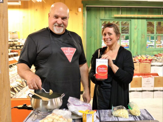 cheese factories owner martin guilbault accompanied by an employee with Swiss fondue dish ready for a tasting fromagerie du champ à la meule notre-dame-de-lourdes quebec canada ulocal local products local purchase local produce locavore tourist