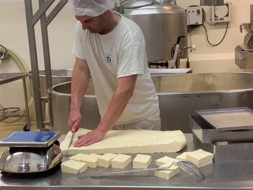 fromagerie un employé en train de couper un gros morceau de fromage sur un comptoir en stainless fromagiers de la table ronde sainte-sophie québec canada ulocal produits locaux achat local produits du terroir locavore touriste