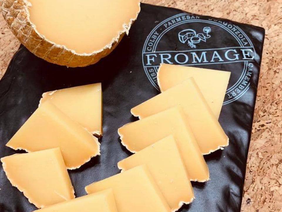 fromagerie fromage parmesan rond avec pièces en triangle sur un papier noir avec logo fromagiers de la table ronde sainte-sophie québec canada ulocal produits locaux achat local produits du terroir locavore touriste