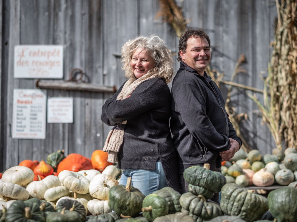 produce markets husband and wife owner of the farm surrounded squash pumpkins of different kinds with old barn in the background la courgerie sainte-elisabeth quebec canada ulocal local products local purchase local produce locavore tourist