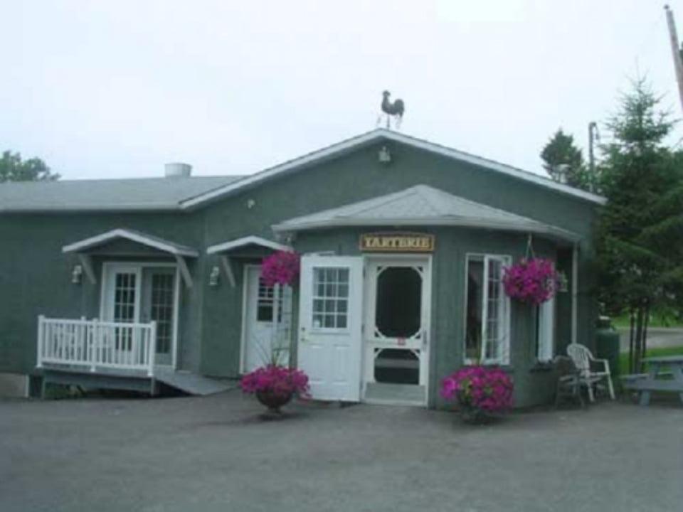 boulangerie artisanale bâtisse de la boutique avec extérieur gris avec fleurs roses à l'entrée tarterie du verger des musiques inc saint-joseph-du-lac québec canada ulocal produits locaux achat local produits du terroir locavore touriste