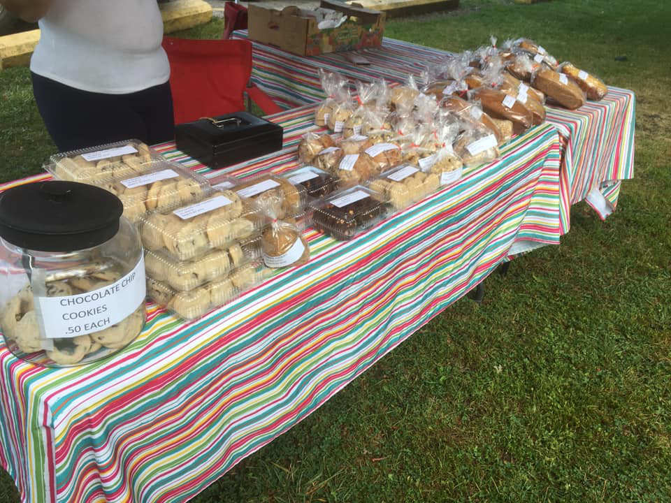 public markets homemade products breads biscuits pastries and even more on an outdoor table with attendant amherstburg farmers market amherstburg ontario canada ulocal local products local purchase local produce locavore tourist