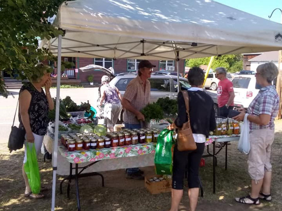 public markets outdoor kiosk of fruits and vegetables with pot of pickles and canings with with customers barry's bay farmers market barry's bay ontario canada ulocal local products local purchase local produce locavore tourist
