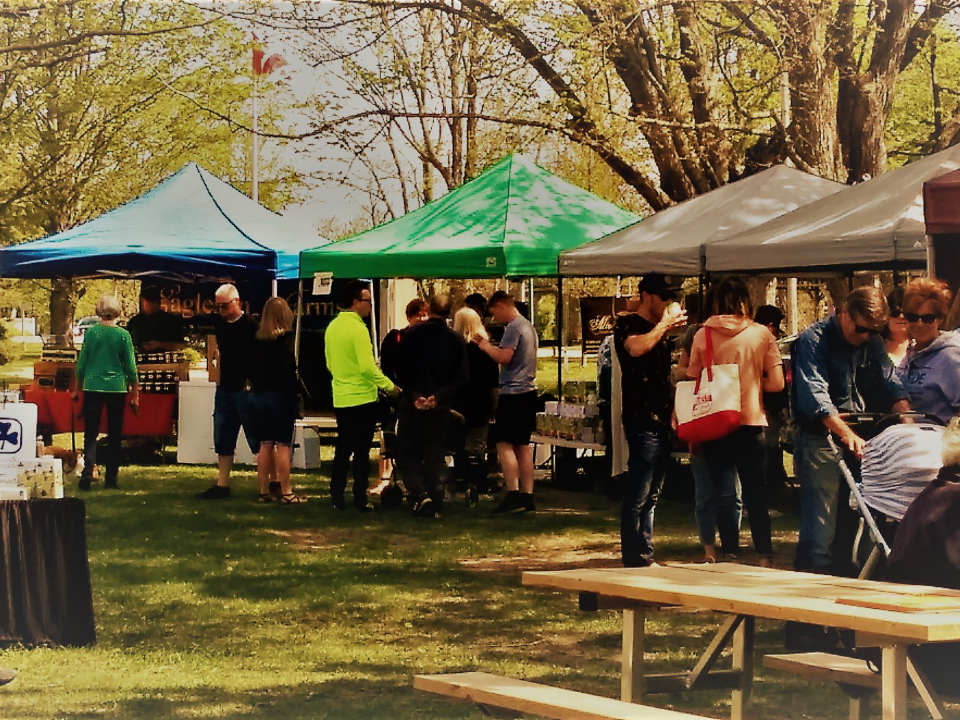 marché public plusieurs kiosques extérieurs dans un parc avec gens sur le site bayfield farmers market bayfield ontario canada ulocal produits locaux achat local produits du terroir locavore touriste