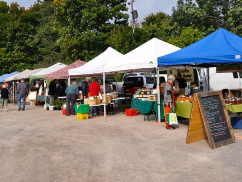 public markets several outdoor kiosks of local merchants with people on the site bobcaygeon farmers market bobcaygeon ontario canada ulocal local products local purchase local produce locavore tourist