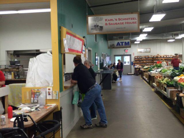 marché public intérieur du marché avec vue sur quelques kiosques de fruits et légumes et de boulangerie et un homme et une femme devant un comptoir de saussices brantford farmers market brantford ontario canada ulocal produits locaux achat local produits du terroir locavore touriste
