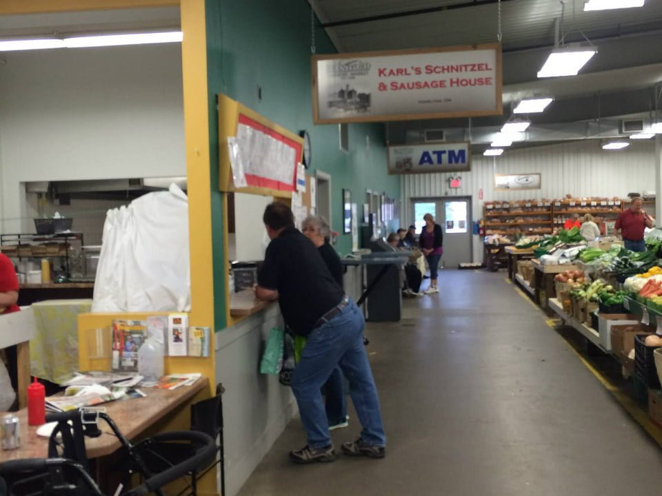 public markets interior of the market overlooking a few kiosks of fruit and vegetables and bakery and a man and a woman in front of a counter of saussices brantford farmers market brantford ontario canada ulocal local products local purchase local produce locavore tourist