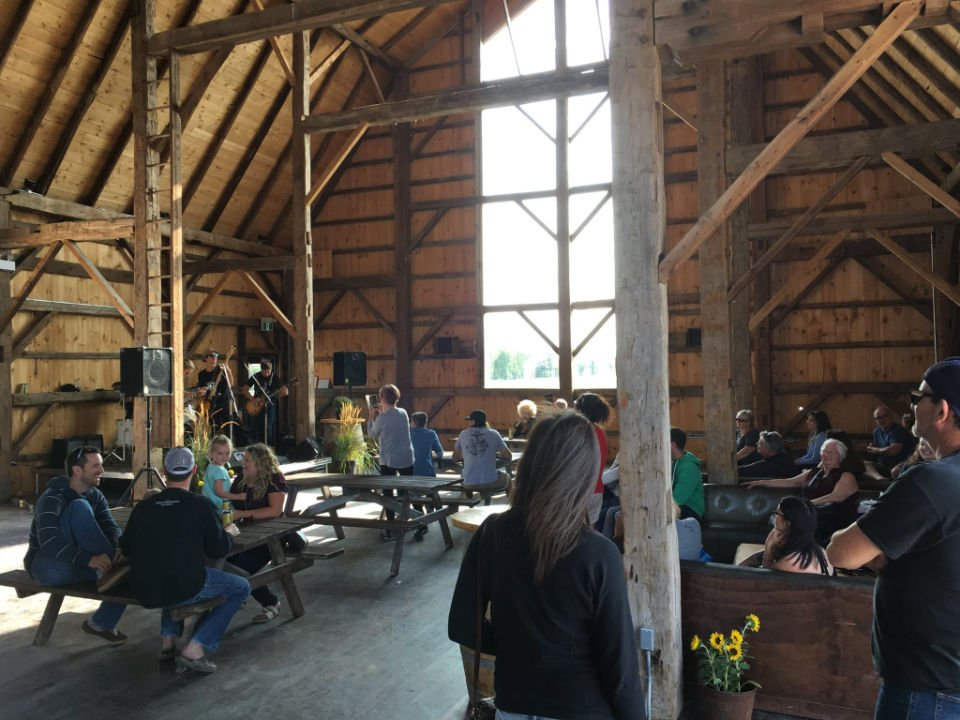 public markets people sitting at picnic tables inside the old barn renovated for events burls creek event grounds oro station ontario canada ulocal local products local purchase local produce locavore tourist