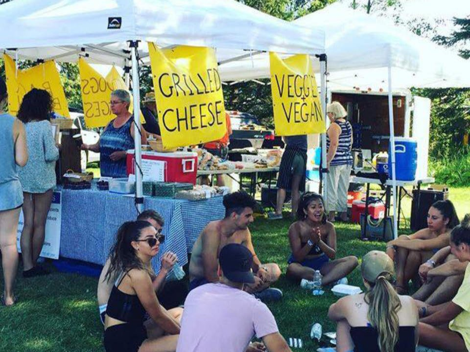 public markets people sitting together on the floor enjoying local food with a food kiosk in the background with customers burls creek event grounds oro station ontario canada ulocal local products local purchase local produce locavore tourist