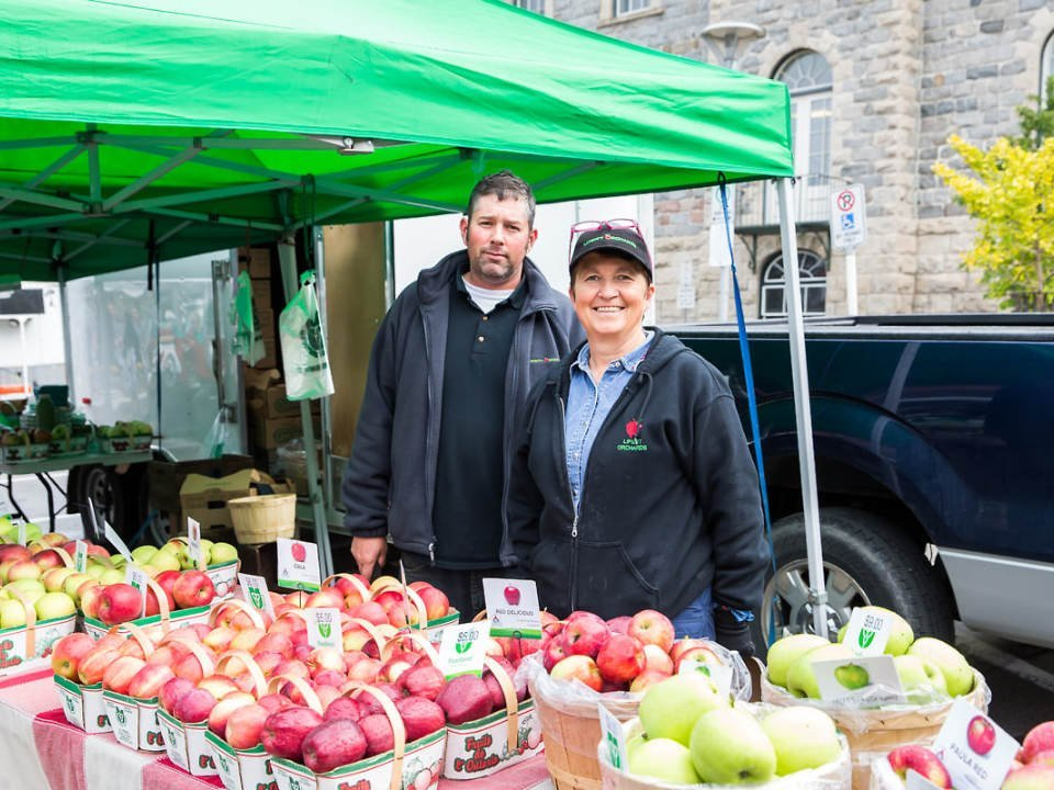 public markets outdoor kiosk with a man and a woman happy to offer their different varieties of apples cambridge farmers market cambridge ontario canada ulocal local products local purchase local produce locavore tourist
