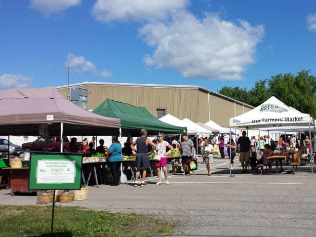 public markets outdoor kiosks of local products in the parking lot of the arena with people on the site clarington farmers market newcastle ontario canada ulocal local products local purchase local produce locavore tourist