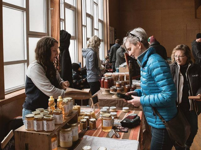 public markets kiosk of donald's honey with dayna busy serving customers collingwood winter farmers market collingwood ontario canada ulocal local products local purchase local produce locavore tourist