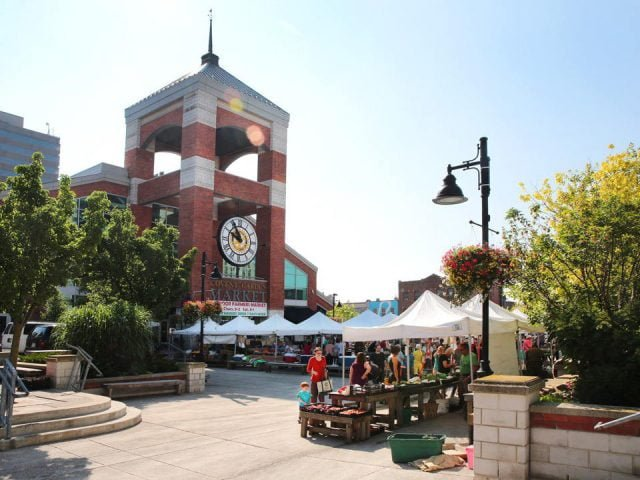 public markets outdoor kiosks of local products with customers on the site and view of the giant clock on the bell tower covent garden market london ontario canada ulocal local products local purchase local produce locavore tourist