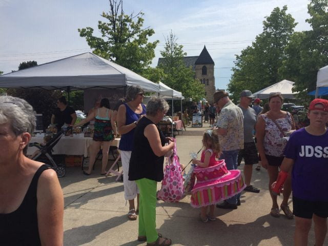 public markets outdoor kiosks with customers on the site and girl with pink dress eat well market hanover ontario canada ulocal local products local purchase local produce locavore tourist
