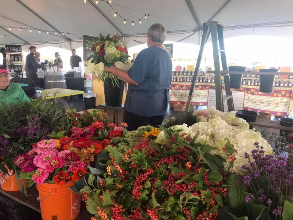 marché public kiosque de fleurs sous la grande tente avec clients farmers market at the village niagara-on-the-lake ontario canada ulocal produits locaux achat local produits du terroir locavore touriste