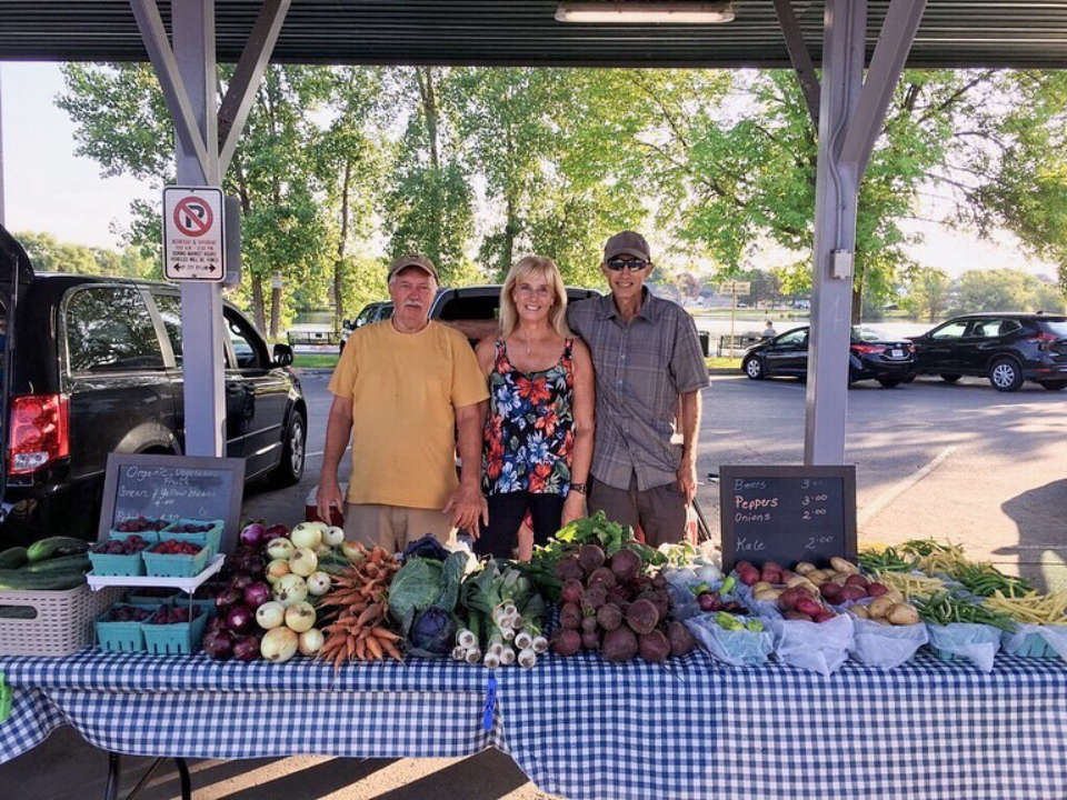 public markets outdoor kiosk of fruits and vegetables with its 3 smiling representatives front street farmers market trenton ontario canada ulocal local products local purchase local produce locavore tourist