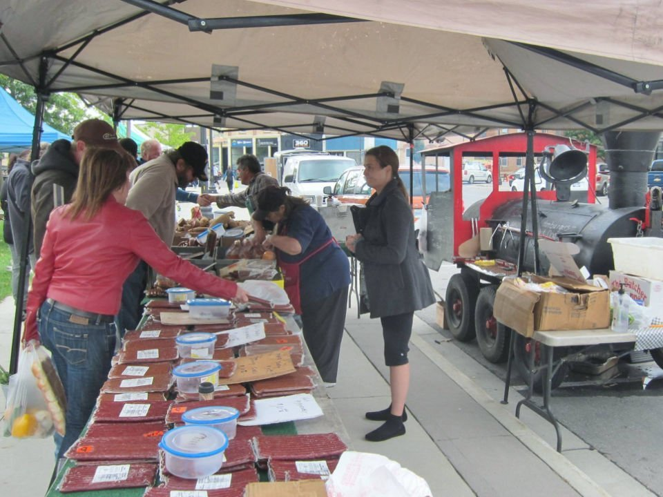 public markets kiosk under the tent of local merchants with people at the tables goderich bia farmers market goderich ontario canada ulocal local products local purchase local produce locavore tourist