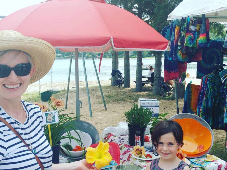 marché public kiosque de vêtements avec femme et une enfant avec la plage en arrière plan lion's head farmers market lion's head ontario canada ulocal produits locaux achat local produits du terroir locavore touriste