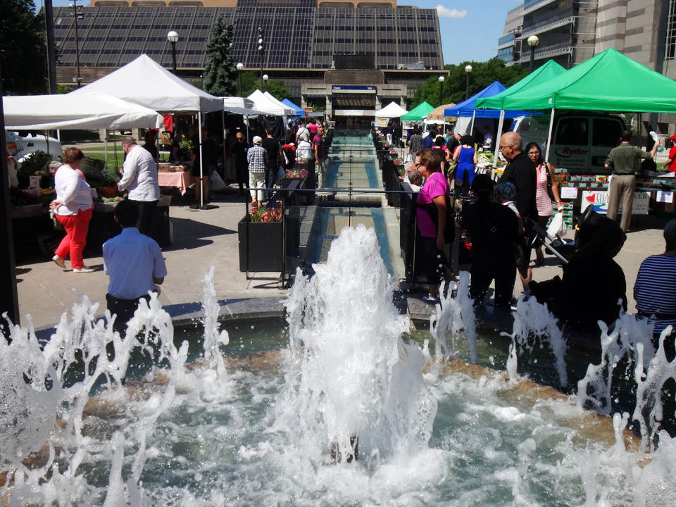 public markets outdoor market with customers at kiosks during a sunny day water fountain north york farmers market north york ontario canada ulocal local products local purchase local produce locavore tourist