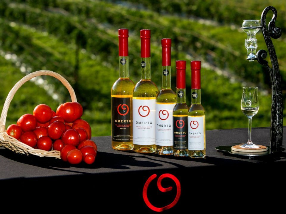 vignoble panier de tomates rouges avec 5 bouteilles de vin de tomate sur une table avec nappe noire et le champs de tomates domaine de la vallée du bras omerto baie-saint-paul quebec canada ulocal produits locaux achat local produits du terroir locavore touriste