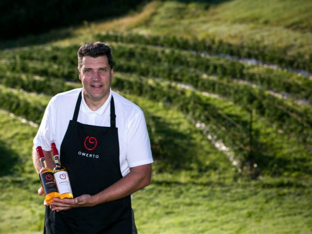 vineyard pascal the owner in the field of the domaine de la vallée du bras with 2 bottles of tomato wine domaine de la vallée du bras omerto baie-saint-paul quebec canada ulocal local products local purchase local produce locavore tourist