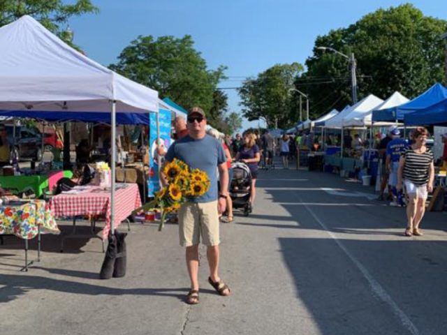 public markets outdoor market with customers at kiosks during a sunny day with a man who has a bouquet of sunflower orangeville farmers market orangeville ontario canada ulocal local products local purchase local produce locavore tourist