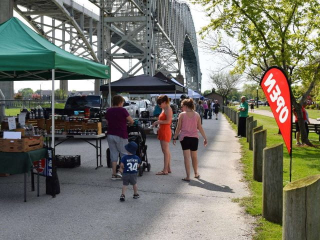 marché public kiosques extérieurs sous le pont bluewater avec gens sur le site point edward moonlight farmers market point edward ontario canada ulocal produits locaux achat local produits du terroir locavore touriste