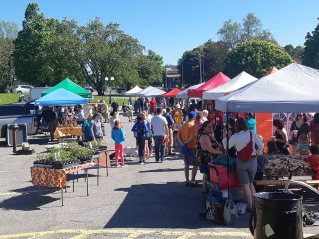 public markets outdoor market in the parking lot of City Hall with people on the site and a beautiful blue sky port hope farmers market port hope ontario canada ulocal local products local purchase local produce locavore tourist