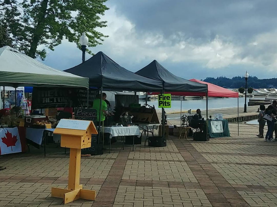 public markets outdoor market on the water's edge with people in the kiosks with a cloudy sky port perry lakefront farmers market port perry ontario canada ulocal local products local purchase local produce locavore tourist