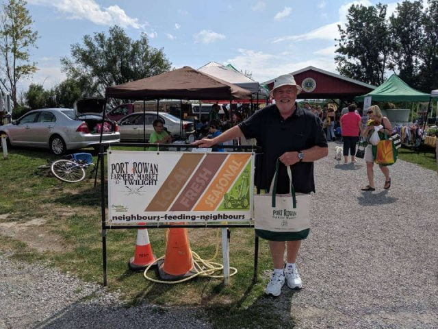 public markets happy customer near the market sign with kiosks in the background port rowan farmers market port rowan ontario canada ulocal local products local purchase local produce locavore tourist