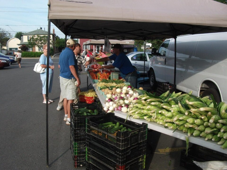 public markets outdoor kiosk of fresh vegetables with customers seaway valley growers farmers market cornwall ontario canada ulocal local products local purchase local produce locavore tourist