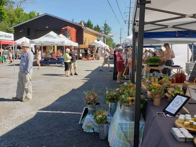 public markets sunny day at the busy market flower kiosk in foreground uxbridge farmers market uxbridge ontario canada ulocal local products local purchase local produce locavore tourist