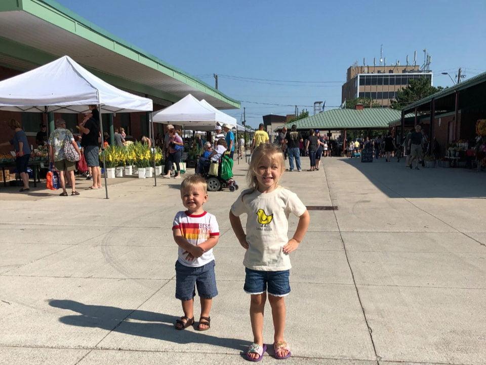 marché public journée ensoleillée avec 2 enfants qui sourient au marché et kiosques en arrière plan welland farmers market welland ontario canada ulocal produits locaux achat local produits du terroir locavore touriste