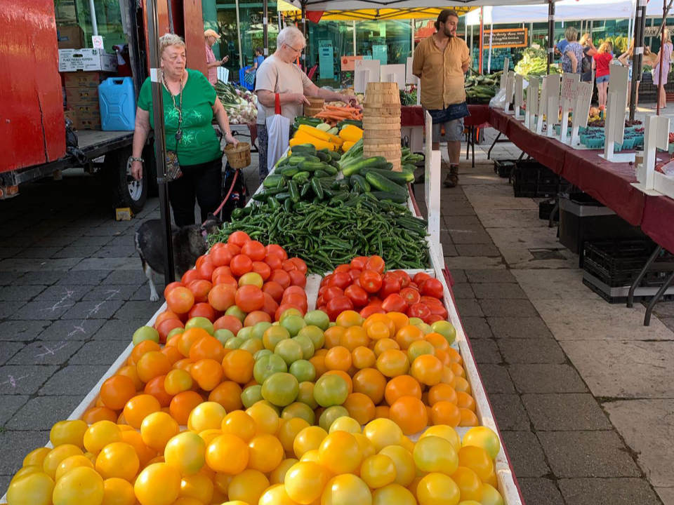 public markets large fruit and vegetable kiosk with clients and his representative whitby farmers market whitby ontario canada ulocal local products local purchase local produce locavore tourist