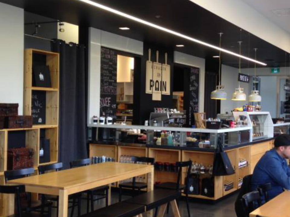 boulangerie artisanale intérieur du café restaurant comptoir de présentation et tables en bois avec bancs noirs boulangerie a chacun son pain baie-saint-paul quebec canada ulocal produits locaux achat local produits du terroir locavore touriste